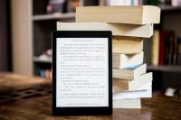 Ein E-Book-Reader steht aufrecht vor einem Stapel Bücher.